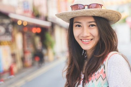 Young Thai woman with hat and charming smile